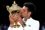 Novak Djokovic, cu trofeul cucerit în la Wimbledon, în 2019