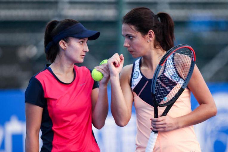 Raluca Olaru și partenera ei de la Shenzhen Open 2020, Dalila Jakupovic,  stabilesc tactica inaintea unui punct. Cele două au ajuns până în sferturile de finală ale probei