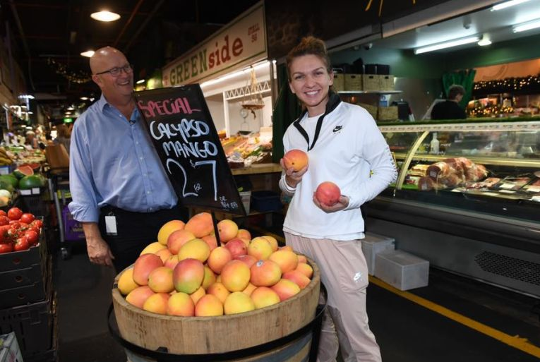 Simona Halep ține bucuroasă în mână două fructe de mango în timpul vizitei din Piața Centrală din Adelaide