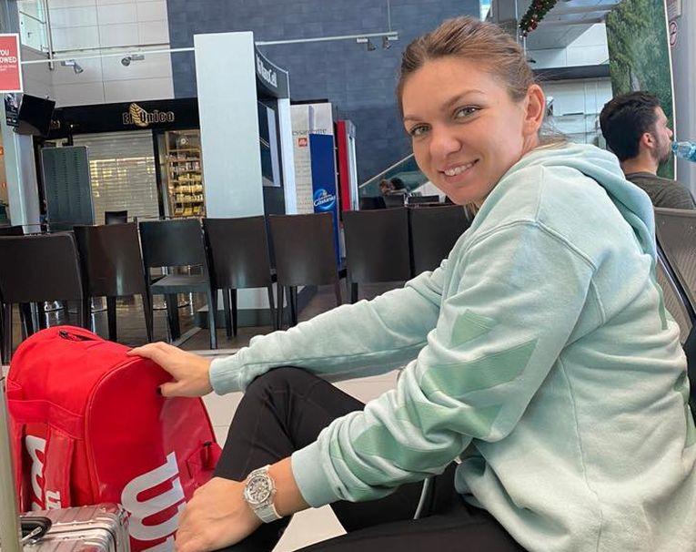 Simona Halep, cu sacul de rachete alături, in aeroportul Henri Coandă, în așteptarea avionului care o duce spre Adelaide